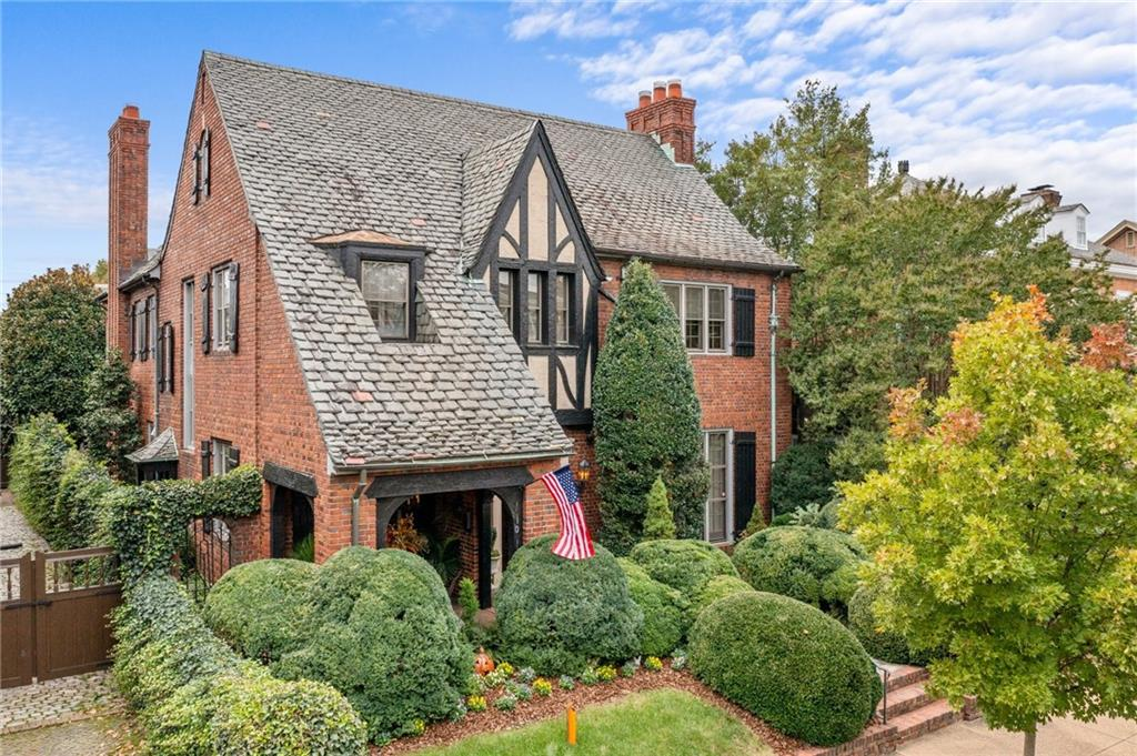 Welcome to this elegant English Tudor home that has been beautifully renovated. Enter into a grand entrance foyer with wainscoting, marble floor & a stunning circular staircase. Continue to the living room, complete with original built-in bookcases & fireplace. The handsomely remodeled kitchen offers custom cabinetry, limestone counters as well as an island & opens onto a family room with a gorgeous stone fireplace. The millwork throughout the home is outstanding & the original plaster friezes located on the first floor are stunning. The owner's suite consists of 3 adjoining rooms that include the bedroom, full bath with shower & soaking tub & a large sitting/TV room with a fireplace & an abundance of custom built-in closets. The 3rd floor is finished and has 2 additional bedrooms, a full bath and a kitchenette, which would be perfect for au pair or caretaker. A rare find in the area, there is a full sized inground pool & well landscaped walled gardens. The detached garage offers a carriage apartment above that has a full bath & kitchenette (not included in sq ft. or room and bath counts above) plus changing rooms & bath for pool guests below.  This is truly a remarkable home!