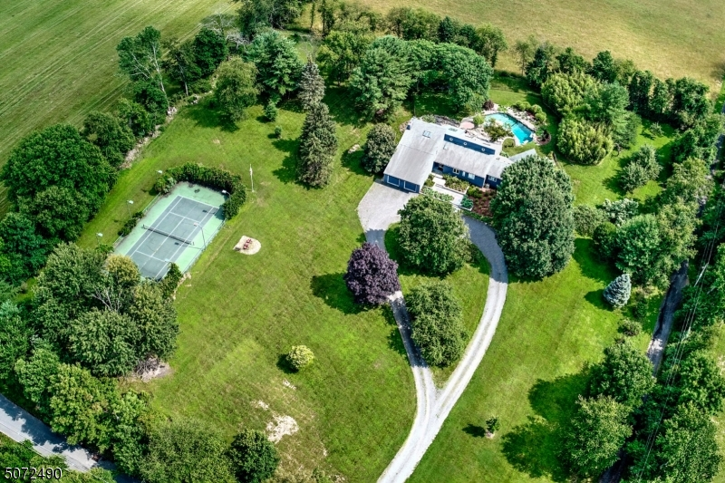 Modern Custom Contemporary deepset on 3.4 Resort- like acres in heart of Tewksbury's horse country. Circular gravel drive, stone surround free-form gunite pool w/ pond bottom & hard court tennis w/lights set this home apart! Transformed 4300+ sqft, 4 bedrm, 3.5 bath, cedar clad home presents liv rm & din rm w/ wind/walls. Entire home remodel offers kitch w/SS appliances & family rm w/stone tile, wd-burning fireplace. Primary-suite added in 2000 w/1000+ sq ft of lux sitting rm, primary bedrm w/dual side fireplace & spa bath. 2 additional bedrms w/shared bath & office/guest rm w/loft & spa bath. Painted natural slate grey (2016) & re-roofed Timberline (2010). Small orchard, variety of apple, pear & peach trees, wisteria & honeysuckle enhance this home. Newer septic
