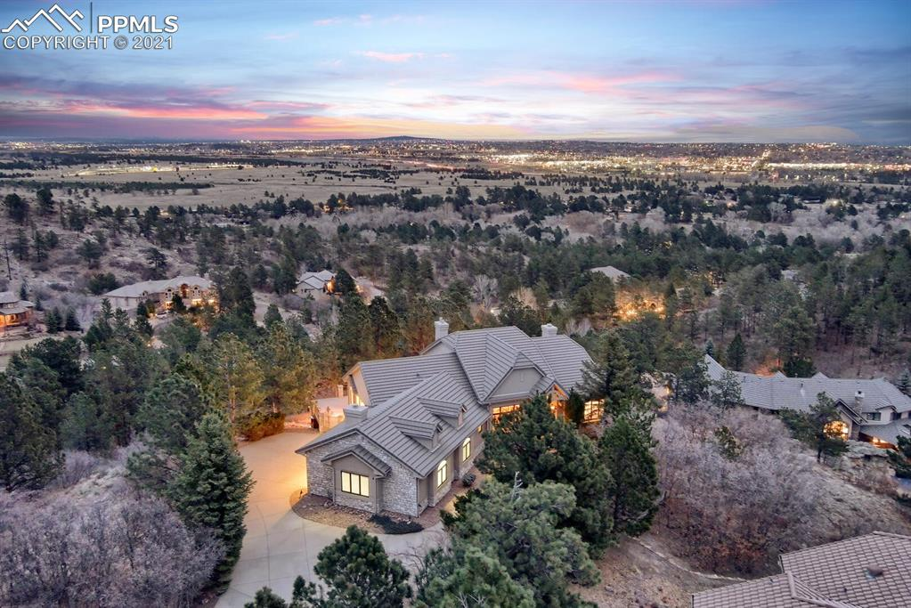 Luxurious custom ranch w/4 beds + study built by Copper Valley Builders on 1 + acres of views, trees & privacy at end of cul-de-sac in desirable Woodmen Oaks in Award Winning School District 20! This home has been meticulously updated & maintained & shows true pride of ownership boasting a one of a kind gourmet kitchen w/hearth room that flows seamlessly to the composite wrap-around custom deck w/wonderful views & privacy amidst the pine trees. The grand entry welcomes you & invites you to enjoy the open floor plan. The formal dining room allows plenty of natural light through the large picture window. Beyond is the great room w/beamed ceiling, gas fp, & walk-out to deck. The perfectly-appointed kitchen will satisfy the most particular chef w/huge center island, newer stainless steel appliances, ample counter space & storage w/walk-in pantry, walls of windows surrounding sizeable dining nook, walk-out to deck & hearth rm w/gas fp. The main-level master retreat w/private, updated spa-like 5-pc bath w/updated counters/tub/fixtures/hardware & huge walk-in closet w/custom shelving, walks-out to private sunroom - the perfect vantage point to take in the spectacular city view. Head downstairs to entertain in the generous rec room w/gas fp, floor-to-ceiling stone work & walk-out to covered patio w/views & wired for a hot tub. The lower level study has built-in desks & bookshelves for an ideal homework spot or home office. 3 sizable bedrooms - 2 w/in-room sink vanities & adjoining shared bath, additional 3/4 bath & huge storage room w/cabinets & shelves & two safes, complete the lower level. This property is truly spectacular w/many features & upgrades to include: oversized finished 3-car garage w/shelving & cabinets, spacious main-level laundry space/mud room w/quartz countertops & newer sink, built-in sound system w/speakers throughout, 2 water heaters, dual-zoned furnace & ac, updated bathroom countertops & newer toilets throughout, fresh paint & much more. A must-see!