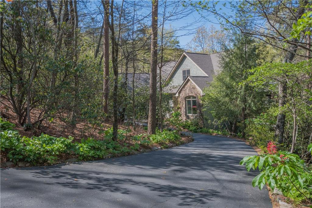 This is an opportunity to own one of the most unique properties in Big Canoe®! Built by an avid naturalist,the fabulous 3.5 acre grounds that surround this woodland oasis make this one of the most private properties in Big Canoe® with over an acre of fenced area suitable for gardening or pets. Enjoy the sound of a rippling stream and koi pond from the screened porch or one of the secluded fieldstone retreats. Indoors, the house has a fabulous kitchen, sauna, potting room/art studio and office.Enjoy mountain views from the privacy of your deck.  Come home to the mountains!