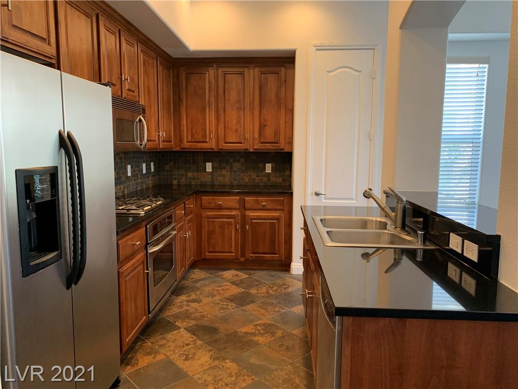 Move-in ready! Within the Manhattan guard-gated community, this corner unit offers lots of natural light and extra space. New wood laminate flooring (100% waterproof) just installed 6.5.21 and entire unit freshly painted. Kitchen includes beautiful cherry wood cabinets, stainless steel appliances, granite countertops, breakfast bar, pantry and slate tile backsplash and flooring. Bedrooms are on opposite sides of unit, each with their own bathroom. Primary bathroom has dual sinks, separate shower, soaking tub, extra storage and walk-in closet. This unit also comes with an assigned underground parking space with elevator access direct to second floor. This urban community has a tremendous amount of amenities including: fitness rooms, dog parks, pool, spa, boardroom, media room, lounge, outdoor covered BBQ areas and more. GREAT LOCATION - the Las Vegas Strip, airport and shopping are minutes away.