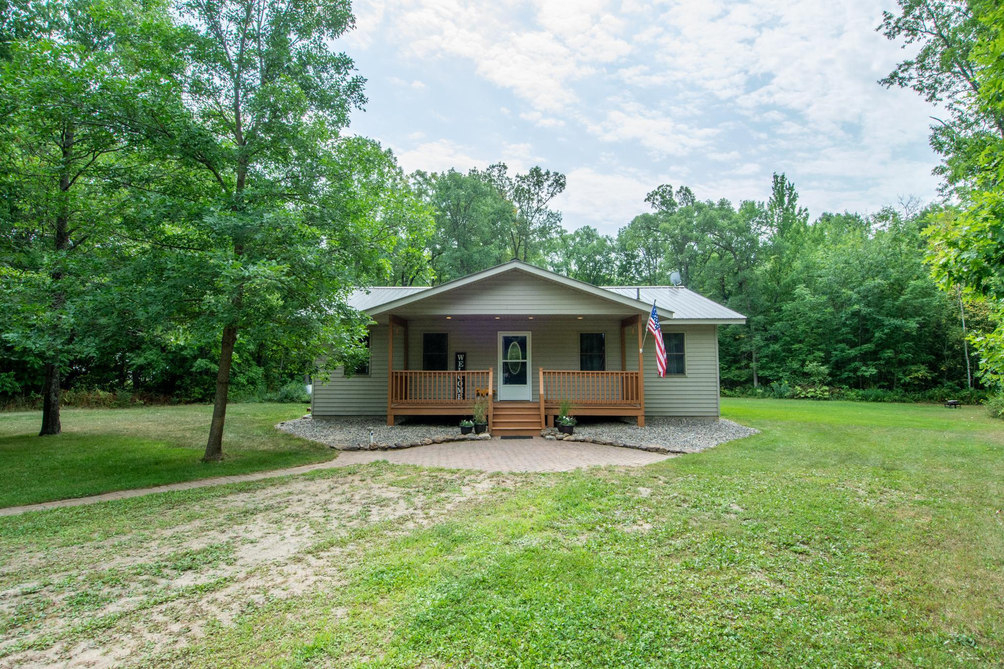 Want to be nestled in the woods on 5 acres? This is your opportunity!! Outside this home features a new septic system that was installed in 2018, a 26x31 garage, covered front porch/deck space, maintenance free exterior siding and roof on both the garage and the house, nicely wooded lot and located on a paved road! Inside this home feature a kitchen with hickory cabinets and breakfast bar, nice dining room space, main floor laundry, living room, a master suite with walk in closet and jetted tub in the master bath and main level features an additional two bedrooms. Lower level features a massive family room space, full bath, storage room and utility room.