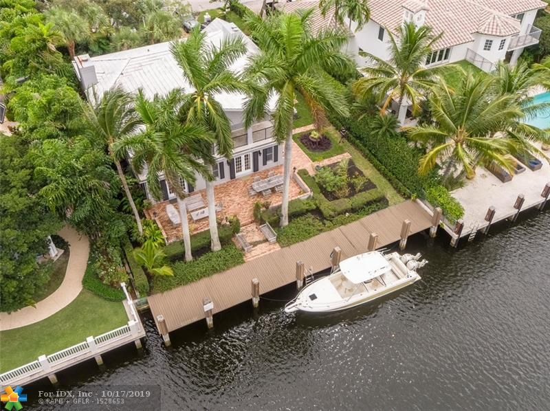 Southern charm at it's finest w/ a soft touch of modern & lushly landscaped. Located in the heart of Rio Vista Isles w/ 75' waterfront, deep water dockage, only few houses from Intracoastal point & minutes to ocean. Enjoy amazing tropical waterfront views w/ no neighboring homes across wide water canal. Master suite located upstairs w/ large sitting room that travels along entire back of house w/ covered balcony. Hardwood floors throughout. Two guest bedrooms w/ private baths upstairs (one guest room has fireplace). Living room, family room, formal Dining room. Gourmet kitchen w/ breakfast nook & garden view. First floor library/den w/ fireplace can be converted into a 4th bedroom with it's own bath. (See PDF attached) PDF attached also shows drawings for a 2nd car garage, pool & more