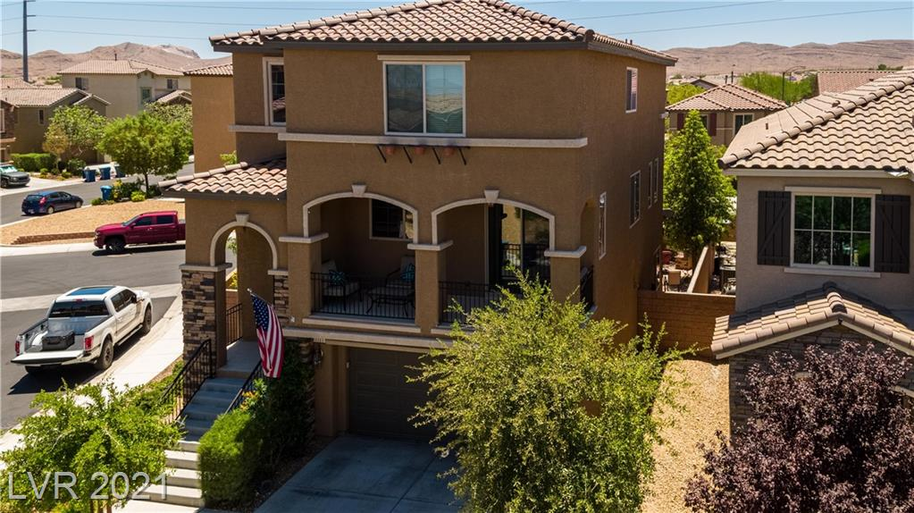 """Stunning three-story home located within a GATED community in the heart of Mountains Edge. Built in 2015, this home has it all; featuring semi-custom 24"""" tile throughout, an open floor plan, and exterior balcony. The kitchen is located on the mid-level and boasts an oversized island perfect for any occasion. Stainless steel appliances, upgraded granite countertops, walk-in pantry with custom wood shelves. and semi-custom cabinets round out this stunning area of the home. The third story contains three bedrooms, all of which are oversized and have ceiling fans. The first level features a massive den complete with a built-in custom made bar. There is also a bedroom with a full bathroom attached. Step outside to the backyard that features a custom built-in fire pit, custom outdoor kitchen, and a large patio cover. The side yard is landscaped with synthetic grass. Sparkling resort style community pool. Just minutes away from schools, shopping, and freeways. Welcome Home!"""