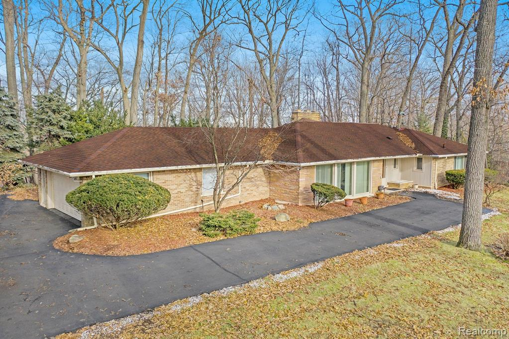 """PRICE REDUCTION presents opportunity for investors to renovate or tear down to build a dream home among multi-million dollar properties in the distinguished community of  """"Kirk in the Hills"""".  Home is situated on two (2) wooded corner lots on top a hill and is being """"SOLD AS IS"""".  Most photos and video were taken before recent storm damage. See Seller's Disclosure.  It's all about location, location, location. Don't let this one pass you by. Located in the Bloomfield Hills School District."""