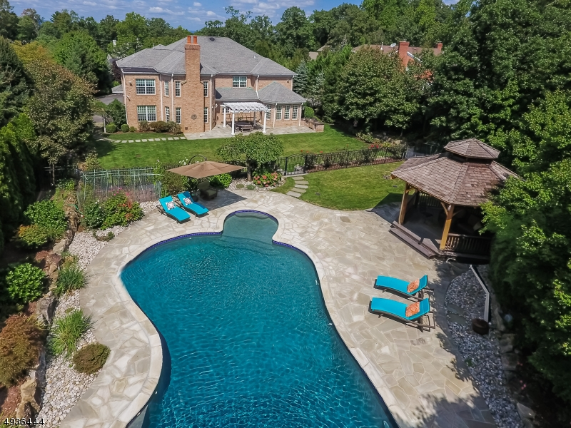 Spectacular Custom All Brick Center Hall Colonial ideally located on prestigious street on .71 acres of stunning park-like property with a gorgeous salt water pool. Designed w/ Feng Shui principles. This stunning home features a grand entrance hall with 20' ceilings, a stunning gourmet kitchen, 2 fireplaces, and a luxurious master bedroom suite w/ sitting room, 2 walk-in closets, & a spa-like master Bath. 9' ceilings on the 1st & 2nd levels. The lower level features an incredible recreation room w/ large wet bar & karaoke sound system, a Billiard room, full bath, & a state of the art Home Theatre with leather seating for 8. Walk one block to highly rated Deerfield Elementary School. Replacement cost would be 4,000,000! Bus service available to Millburn Middle & High schools. Tax appeal owner won!