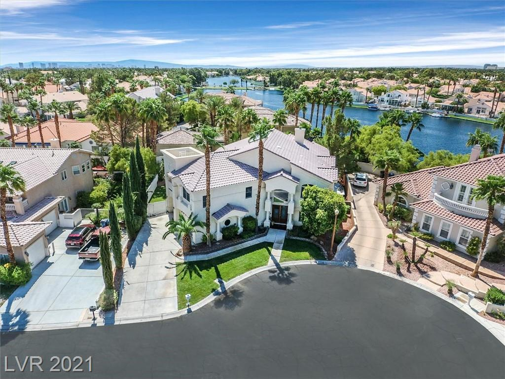 """Embrace the ineluctable elegance and grandeur of this semi custom gated Diamond Bay home in the vibrant lakeside community of Desert Shores with its 4 man made lakes, private lagoon beach and park. Replete with marbled entry foyer with marbled columns, and skylit atria """"garden"""" room, its 3 fireplaces, and soaring ceilings, this is a unique and beautiful home.  Enjoy panoramic mountain vistas from your primary suite balcony or lake views from your upper level perch.  5th bedroom or office down. Soak fireside in your primary bath jetted tub or refresh in your primary bath steam shower.  Modern white chef's kitchen boasts new stainless dishwasher, Subzero fridge and granite countertops. Breakfast area opens to covered patio. Close proximity to sports venues, upscale dining and shopping, and a short Uber to the Las Vegas Strip. Your jewel in the desert awaits. Imagine the serenity of Desert Shores 4 lakes and private lagoon beach at your fingertips and start packing!"""