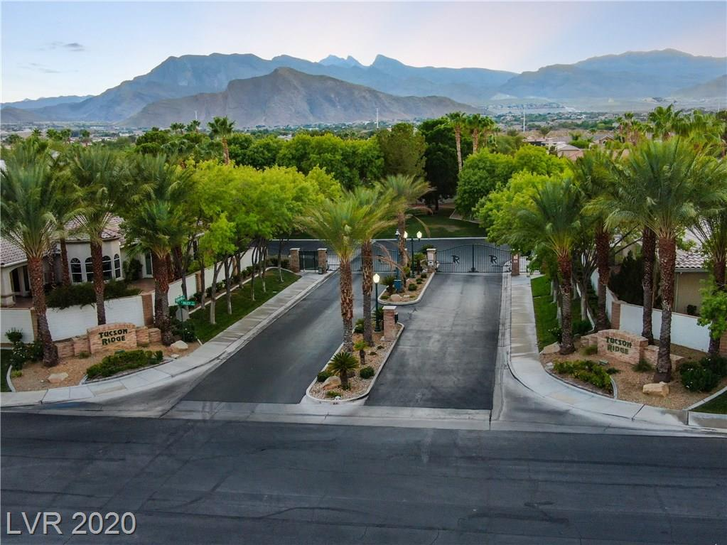 At the edge of Mountain Crest Region park, the gates of Tucson Ridge welcome you with tree lined streets, a gazebo park, tennis court and 90 all custom homes. Amidst this enclave awaits your 3690 Sg ft single story pool home on nearly .5 acres!  Upon entering the home, one is struck by the 12 ft ceilings, 8 ft interior/exterior doors and the oversized windows that create a magnificent light and bright open concept living experience.  Separate from the enormous master suite complete w/its massive custom closet, the subsequent bedrooms are spacious and feature great closet space as well!  New quartz countertops and marble back splash add the perfect compliment to the new S/S appliances. Nothing says custom/Luxury home like a built-in *Monogram Refrigerator/freezer!  There are new pavers on the walkway and driveway that lead to the newly epoxied garage floor. Don't walk, RUN to view this gorgeous home in this extraordinary Lone Mountain Rural Preserve community priced below recent comps!!
