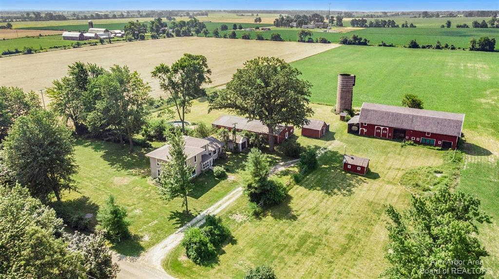 Enjoy idyllic country living just minutes from Saline, Tecumseh, and US-23 on this picturesque 15-acre farm with updated 3000+ sqft farmhouse, barn, and several outbuildings! The home has the perfect mix of classic farmhouse touches like thick moldings, wood floors, and an enclosed porch with modern conveniences like an updated kitchen and bathrooms, new sump pumps and water heater, and a generator. Main level provides a sprawling LR with bay window and attached bedroom/study, a renovated open kitchen and dining area overlooking the enclosed porch and 2nd entry, and a family room with 3rd entry, half bath, and attached sunroom with access to the massive deck. Upstairs you'll find 3 more generously-sized bedrooms. The primary suite has its own private full bath with spa tub surrounded by windows and separate shower. Two more bedrooms share a 2nd full bath upstairs, including one with an attached office/playroom/nursery. Daylight basement off family room could be finished into another ho