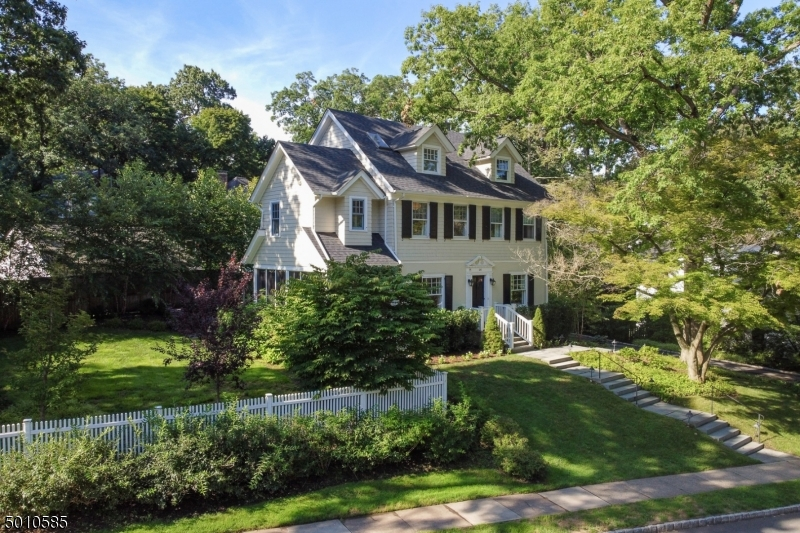 Cosmopolitan appeal! 5BR/3.1FB Colonial has been renovated to perfection while keeping the beauty of its traditional 1900s character. 9ft ceilings, distinctive moldings & dark floors - amazing fl plan allows for both max living and entertaining space. Gourmet kitchen w/ SS appliances, marble counters & banquet adjoins chic FR, screened Porch with chevron tile flr and bead board & LR w/ gas fireplace. Office & 5 spacious BRs occupy 2nd/3rd levels. Mstr suite has lux bath & lrg closet. LL: Rec rm, laundry & mud rm. ALL NEW: roof, electric, carpets, security system, front landscaping, refinishd wd flrs. Lush yard, bluestone patio, firepit, profess landscaping & tall trees. Located on friendly North Side, home is just  blocks to downtown, NYC trains, Starbucks, top schools, Farmers Market, restaurants & boutiques
