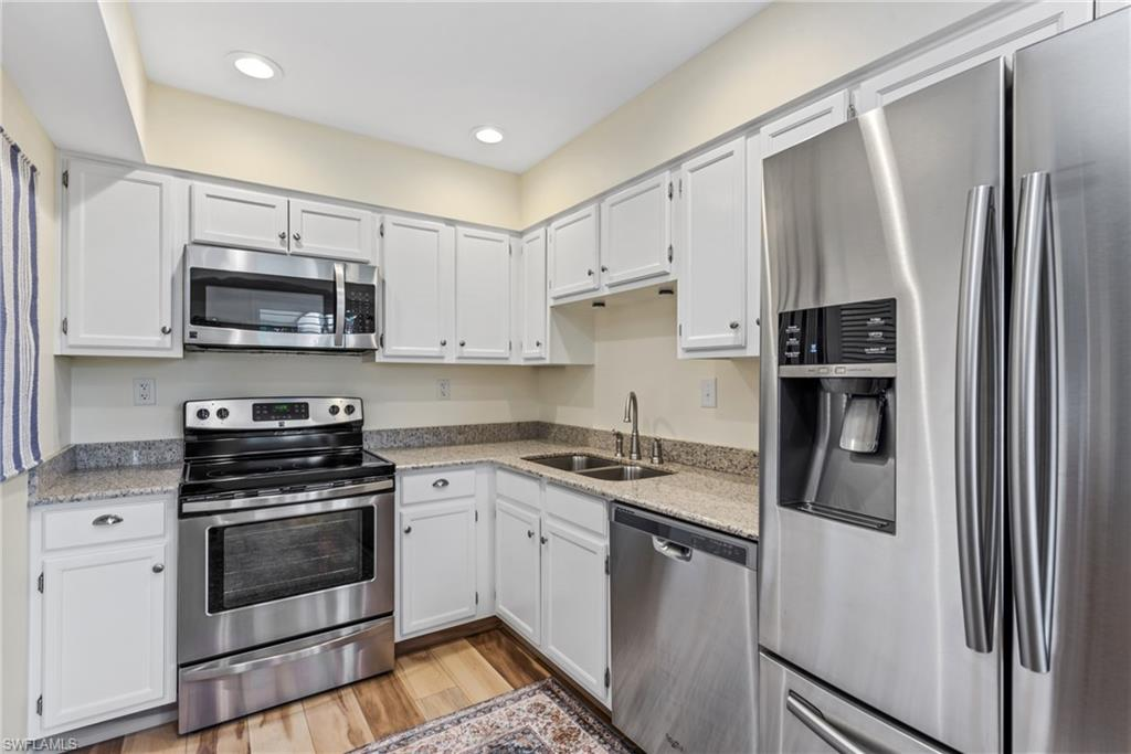 Beautifully Remodeled End Unit! New Wood-Look Tile Flooring, Carpeting, Kitchen Countertops, Appliances, Paint, Light Fixtures and Bathrooms. Seller also added attic storage space, extra R30 insulation, water faucet on lanai and Laundry Sink. Unit also has Impact Glass Sliders and Windows. Private Preserve and Golf Course Views. Popular community with 2 pools. Recent improvements include new exterior and hallway paint, screened doors, lanai screens and landscaping. Close to Marco Island and Naples Beaches!