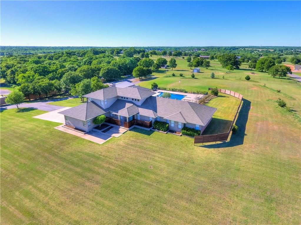 Views for Miles! 5 Acre estate w/ gated drive sits high on a hill for incredible scenery in every direction. Stunning black-bottom pool w/ fountains & multiple seating areas. Completely renovated home interiors, updated kitchen & baths, Bamboo wood floors throughout entire home. Cozy Den w/ amazing natural light and windows to take in the views. Multiple living areas, down, 4th bedroom has been converted to craft/play room w/ custom built in storage, could easily be closets if needed. Study off master, His & Hers Closets in the HUGE master bathroom. Upstairs 2 Beds each with their own bathroom and a kids loft w/ built-ins. 30x40 Shop Building, w/ 8ft doors, 100 Amp electric service. Plenty of parking, gravel storage area. This property has been fenced for horses previously, irrigation for quite a bit of the acreage. Very few properties w/ this many updates + pool + land. Hard to find in East Edmond! Covered 40 x 10 Chicken Coop Run with automatic door entering into 12x12 Indoor Coop.