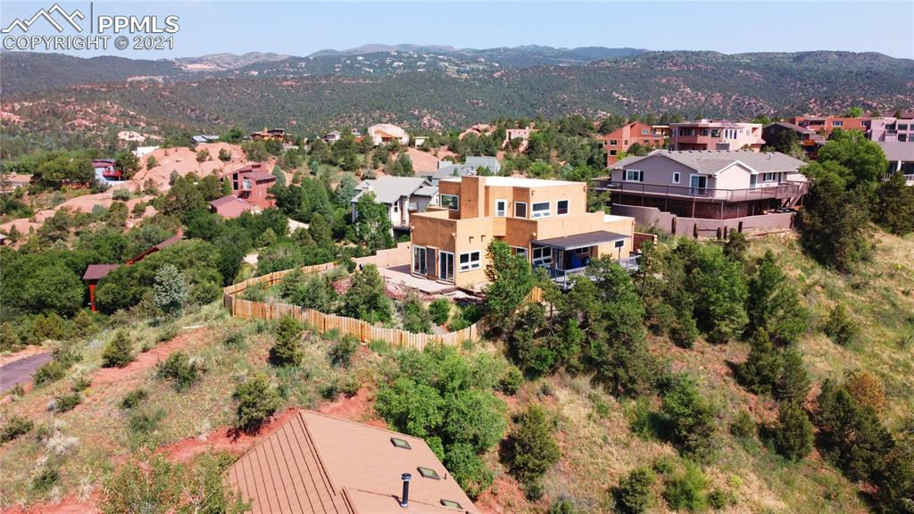 Experience this SPECTACULAR property with 360 degree views of front range & Pikes Peak and the rocks of Garden of the Gods!  And it includes a wonderful well maintained stucco home! The home is enhanced with a large 10x34 covered Trex deck to the east, a 9x17 Trex patio to the south & a 15x29 stamped concrete patio to the west, all with beyond amazing views! Entering the home, you will step into a great room with newly finished pine wood floors, a stone,gas fireplace, easy access to the kitchen with solid surface counters, stainless appliances & a large pantry plus a separate dining area.  A 14x15 room off the living room creates a wonderful office space or art studio and walks out to patio to the south.  Two bedroom on the main level have both been newly carpeted.  Additional features:  Freshly painted throughout, whole house water filter, vinyl windows/doors, pet friendly fenced area, two five piece baths (one on each level), large master bedroom with gas fireplace opening to very large bathroom and 10 x 16 walkin closet.  Six doors open to the outdoor living space, easily accessed from most rooms.  The two car garage features a temperature controlled wine room This property is close to Manitou Springs, shopping, Garden of the Gods and Old Colorado City.
