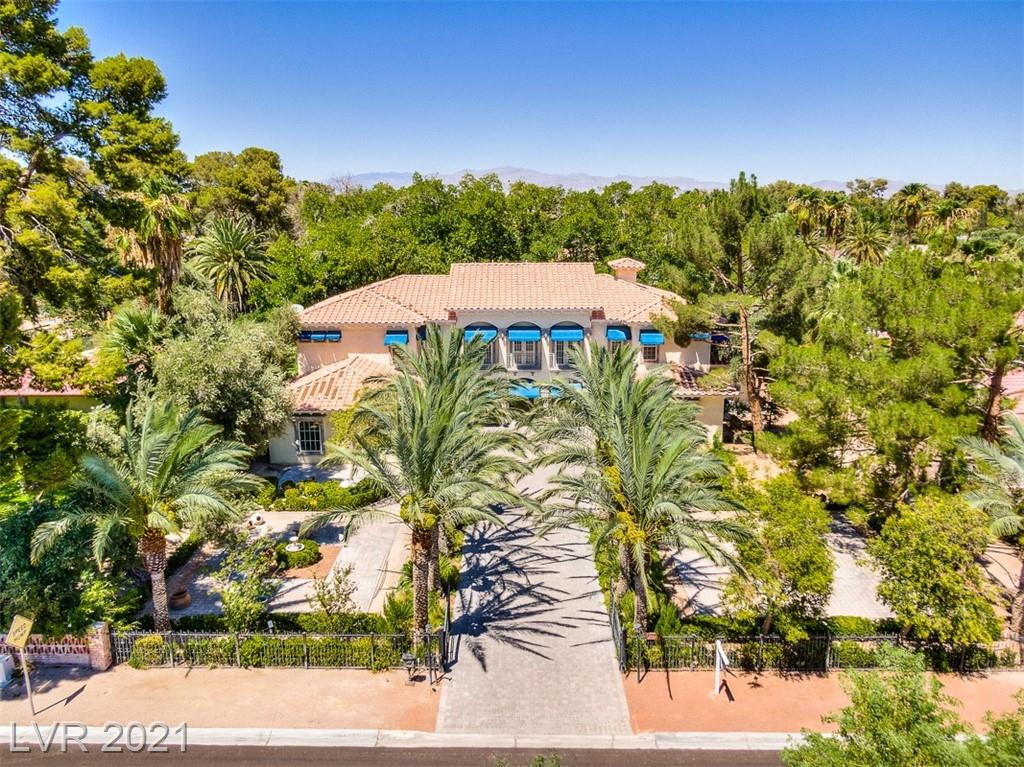 Las Vegas luxury home sitting on a .91 acre lot! This floorplan is over 7,000 square feet, features a separate casita, and is zoned for horse property. Enter through private gates to view this luxury home with no HOA! Original owners. Main home features a large front patio, perfect for entertaining. The great room features floor to ceiling windows and a wet bar. Bedrooms on both levels of the home. Spacious kitchen features a large island, black Viking stove, and two dishwashers. The second level hosts the primary suite with a wet bar and private balcony, and features 10' ceilings. Travel to the casita where you will find two additional rooms and a bathroom. The casita is currently being used as a workshop and offers endless possibilities! Enjoy the unique air conditioned tree house and Tennis court with full lighting. Pool and spa - perfect for diving board to make for fun summer days! This home is waiting for your personalized touch! Schedule a tour to view this Las Vegas home today!