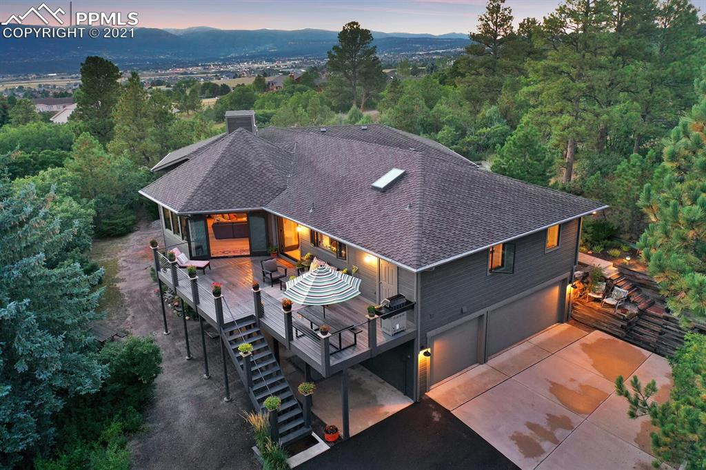 THE PERFECT TRIFECTA - VIEWS, TREES, AND SUNLIGHT! This 5 bed, 3.5 bath, 3 car garage boasts views of the Divide, Pikes Peak, and USAFA.   Enter this beautiful home through a private garden patio area. As you open the 6 pane french entry doors you will be greeted by magnificent mountain views,  open concept floor plan & vaulted ceilings w/ custom beams & accents. Hexagon shaped great room features an Xtrodinair linear gas fireplace and 3 sides of glass windows/doors. An open formal dining room adjoins the gourmet kitchen making this area perfect for entertaining. Beautiful 9 inch French White Oak Floors, Alder Cabinets, Quartz Countertops, Maple Butcher Block Cooking Island, KitchenAid appliances, Beverage Cooler, 2 Convection Ovens and hidden under cabinet lighting & outlets make this kitchen one you will never forget! The 18'X8' walk-in pantry is a dream. Laundry room, w/sink and 2 storage closets, is just off the pantry. 2 sets of french doors lead out to a 516 SF composite deck with cable railings allowing you to enjoy the EXPANSIVE views. The main-level master suite boasts views, a large walk-in closet w/ custom shelves & drawers along with a luxury bathroom featuring custom concrete accents, soaking tub & skylight. 2 more bedrooms on the main floor: one has an ensuite bathroom perfect for guests while the other room has wall-to-wall shelves - making it a great main floor office or a 5th bedroom. Spectacular lower level space with separate entry, rec room, gas fireplace and kitchenette makes for a perfect 2nd entertaining space or potential mother-in-law suite. Lower level bedrooms have walk-in closets. Storage galore; large hallway closet, under stair storage and massive 24x13 seasonal storage in the crawlspace. Extras-- Milgard Ultra Fiberglass Windows/Doors, Troy/Mitzi/Hinkley/recessed lighting, Grohe fixtures, and Nest Smart Thermostat. You will not want to miss the VIEW HOUSE near award-winning District 38 schools, open space and I-25 access