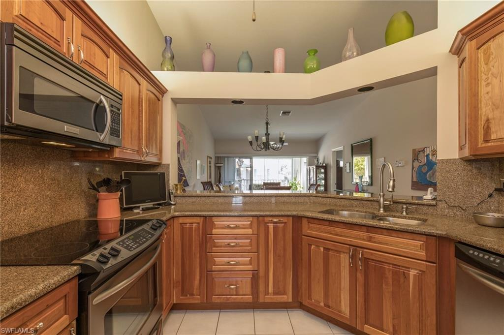 C.15894 - This second floor end unit has volume ceilings and is centrally located in the community.The kitchen features granite countertops, warm cherry wood cabinets, and stainless steel appliances. There are plantation shutters, wood and tile floors throughout.  Both bathrooms have also been nicely updated. There are two lanais, the larger one featuring a jennair grill and overlooks a serene water feature. A one car detached garage and guest parking is in front of this unit. Additionally, for those that want a second floor unit but are concerned about climbing the stairs, there is an electric stair lift. The community features a community pool, clubhouse and brick pavers. Beyond the community, Pelican Bay has 2 private beach clubs with restaurants, tram shuttles to the beaches, fitness center, community center and 2 location of tennis courts which are included in your fees and an optional 27 hole championship golf course. Pelican Bay is close to Waterside Shops, Mercato and the Ritz Carlton.  Make your appointment today to see this fabulous home.