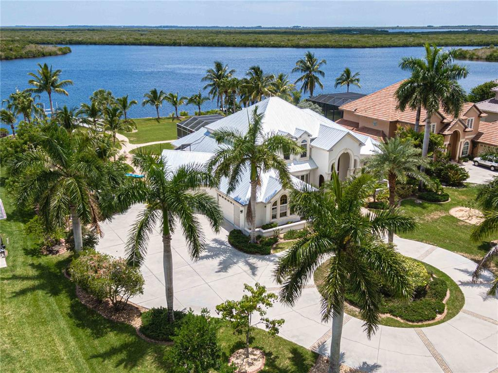 Spectacular custom built estate home located in the coveted South Bayview Estates. 135 feet of waterfront with no fixed bridges and the much sought after southern exposure. Direct access to the Gulf and open water makes this a boater's paradise. Pass through the private, gated circular driveway to this stunning 4 bed, 4 1/2 bath plus office, library and private guest suite. The majestic mahogany double door leads you into the dramatic foyer with a grand staircase. Enjoy panoramic views of the water through the expansive aquarium-style windows found throughout the home. The gourmet kitchen, featuring rich cherry wood cabinets, granite countertops, gas range, desk area, and breakfast bar, is open to the family room and has access to the lanai. Enjoy your coffee at the breakfast nook and then dinner at the impressive pillar-lined dining area. Thoughtfully designed, the 2 guest bedrooms, both en suite, are located on the first floor, allowing for privacy for all. If your guests prefer a bit more privacy, the home features a 1 bed, 1 bath guest suite which is conveniently located just off of the lanai and outside bar area. Upstairs, the grand master suite with unobstructed water views is connected to a sitting area/library. It comes complete with wet bar, huge walk-in closet with built-ins, dual sinks, Roman shower and jetted spa tub. Step out onto your private terrace and down the spiral staircase to enjoy your oversized lanai, sparkling heated pool and spa. Perfect for entertaining your guests. Bring your water toys -- there's plenty of room for them. A 10,000 lb. boat lift, jet ski lift and ramp for your kayak can accommodate it all. Other impressive features include a NEW roof, 4-car garage, gas fireplace, tray ceiling & crown molding throughout. Welcome to waterfront living at its finest.