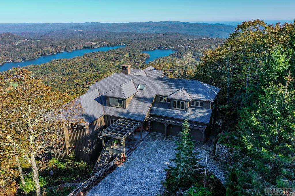 This +/- 8,000 sq. ft. majestic home is located on top of Toxaway Mountain with stunning, panoramic views of the Blue Ridge Mountains and Lake Toxaway. This 5 bedroom, 4 1/2 bath home is the perfect home for entertaining with its double spacious decks to enjoy the views and cool summer temperatures. The wall of glass windows allows plenty of light throughout the home. This home has many features including a spacious gourmet kitchen with separate butler/food pantry, a dining room area, three fireplaces, and a laundry room. Enjoy the double sided stone fireplace that adjoins the living room and dining area.  This home features a master suite with a walk-in/roll-in shower and spa tub and walk-in closet. There are three guest bedrooms located on the lower level, a den, wet bar and small kitchenette. The fifth bedroom is located on the upper level and can be an in-law suite with its own kitchenette, an office, an art studio, or any combination of possibilities.  This home is handicap accessible and has an elevator that conveniently services all three levels.  The home has a three-car garage, a large cistern, a slate roof, and an expansive parking area with stone pavers. The owner has added a 48kw Kohler generator along with numerous upgrades. All of this is perfectly situated on  +/- 2.91 acres. This home is truly a must see!  Bring your boat, friends and children for a fun day on the lake or enjoy the numerous amenities offered at Lake Toxaway!