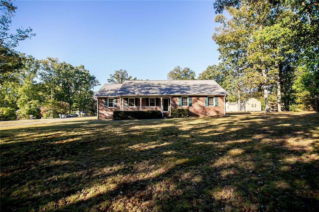 Welcome to 1912 Belleau Dr located in sought after Bon Air! This 3 bedroom, 2.5 bath, 1913 sf all brick rancher rests on over 3/4 of an acre and is built to last! Step inside to find beautiful hardwood floors throughout most of the home. Family room features carpet, a brick wood-burning fireplace, exposed beams and opens to the eat-in kitchen. Kitchen features solid wood cabinets and ceiling fan. A sunny Florida room overlooking the rear yard provides ample natural light and leads to the covered rear patio. Back inside, down the hall are all three bedrooms - the primary suite has a private full bath with zero entry and the two additional bedrooms are serviced by the full hall bath. Additional features include: newer roof, replacement windows, whole house generator, freshly painted interior, and two detached sheds (one is partially finished that could make a perfect home office). Conveniently located to shopping, restaurants + interstates.