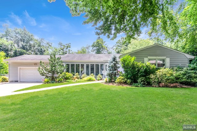Spectacular expanded ranch home in Tenafly! Meticulously maintained home gorgeous park-like setting. First time offered on the market. Elegant and generous sized living room, gracious formal dining room, updated modern kitchen, sunny and bright breakfast room, and family room with wood burning fireplace. Sliding patio doors leads to the large paver patio overlooking the beautiful backyard for effortless indoor/outdoor entertaining. Primary bedroom ensuite, two additional bedrooms and full bath, and spacious linen closet in the hall. Fully finished lower level has library/office ideal for working remotely, full bathroom, and large, open recreation room lined with two walls of built-in closets for ample storage. Beautiful, professionally landscaped  garden with mature plantings and in-ground sprinklers.  Surrounded by multi-million dollar homes. Perfect location-minutes from everything- Blue ribbon Tenafly public schools, parks, shopping, and easy commute to NYC. Move-in condition!