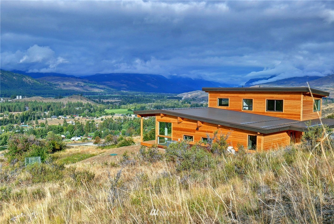 Versatile contemporary home w dramatic views! High ceilings open to spectacular views through a wall of windows. Appealing mixture of wood siding, distinct reclaimed wood cabinets & trim plus lg wood beams are complemented by innovative touches of quartz flooring & counters & vintage lighting. Deluxe master suite on main floor! Custom kitchen w hi-end appliances. 2nd bdrm & flex rm. Adj 148+acres of Open Space & future trails to Winthrop. Only minutes to Winthrop and Nordic trail system.