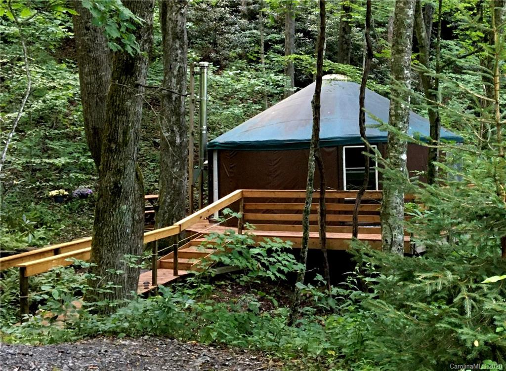 Rare opportunity to own a yurt, tucked away in an idyllic mountain setting. The front deck sits just above a pristine stream that flows down the mountain. Relax to the sound of water and view of lush flowering rhododendron and carpet of ferns. The tree canopy helps hold the cool air from the creek around the yurt site. Warm up in the fall and winter with an efficient wood stove. Stone wall and paths create a park like setting that make this a perfect getaway. The yurt has been used as a music studio and features a loft as well as kitchen area, small room and larger open space . There are 2 double hung windows and 4 plastic windows. Due to the narrow foot bridge across the stream, children must be closely monitored and enter at their own risk. Do not walk around the back of the yurt where there is no railing. ***Call Listing Agent prior to showing***