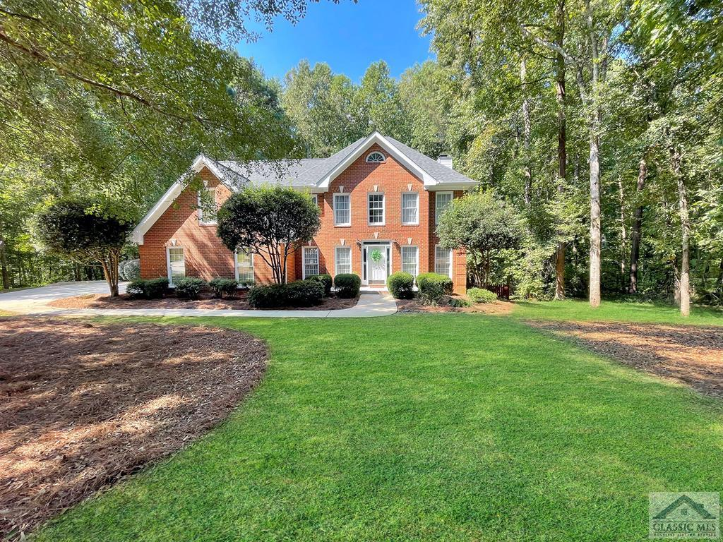 Fabulous 4-Sided Brick with 4 bedrooms, 3 full bathrooms, HUGE BONUS room above the garage, plus an unfinished basement, and a fenced backyard.  This Oconee County home with an Athens address is located within 10 minutes to UGA and FIVE POINTS.  Step in the front door of this great home with a Living Room to the right and the Dining Room to the left.  Walk down a short hallway to the spacious Great Room with a fireplace, built-in shelving, and lots of windows with natural light on the back side of the home.  The Eat-In Kitchen has lots of cabinet and counter space with Quartz counter tops.  There are hardwood floors throughout the living spaces on the main floor and carpet in the one bedroom on the main which has a full bathroom.  The pantry closet is between the Kitchen and the two car garage.  The expansive deck is an oasis for your outdoor gatherings along with an AMAZING screen porch with great views of the fenced backyard.  Upstairs is the large Master Bedroom with a trey ceiling and Master Bath with a double vanity, separate shower, garden tub along with a walk-in closet.  There are two more bedrooms upstairs along with a full bathroom and utility room, which has cabinets above the washer and dryer.  At the end of the hall is a HUGE Bonus Room.  The basement is unfinished yet stubbed for a bathroom, along with a patio below the deck.  A small creek is behind the fence.  The property line is on the other side of the creek.
