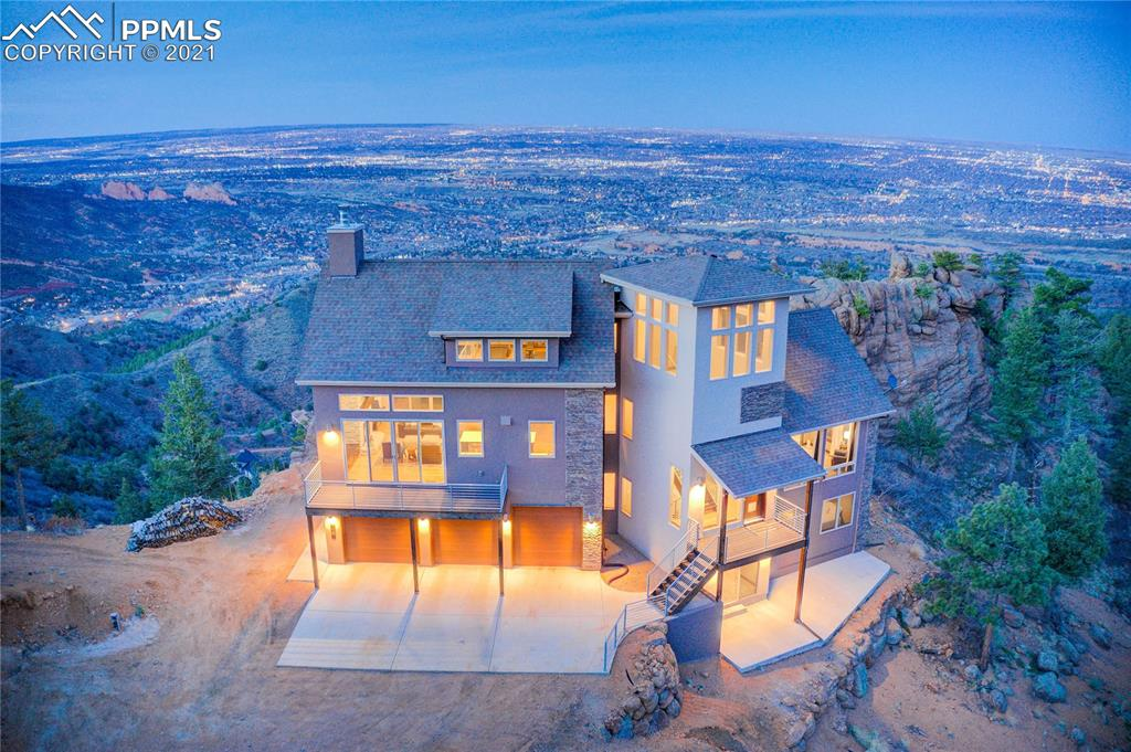 Stunning top-of-the-mountain home in the 2000-acre gated community of Crystal Park offers everything you can imagine! Located 10 minutes from the gate, this home greets you with 360° views of the mountains and Colorado Springs. Natural light and beautiful maple wood flooring lead you through the magnificent open floor plan. A floor-to-ceiling stack stone wood burning fireplace, vaulted T&G ceiling, and double walkouts decorate the cozy living room. Enjoy homecooked meals in the gourmet kitchen decorated with high-end stainless-steel appliances, quartz counters, and shaker-style sable brown soft-closing cabinetry. Access to the dining area equipped with a wet bar. Experience instant comfort in the owner's retreat with an adjoined bath that is to die for! The 5-piece bath offers a double vanity with quarts counters, a walk-in closet with a private walkout and separate washer and dryer, and the heated flooring is perfect for those cold winter nights. A secondary suite offers an adjoined full bath with a built-in linen closet and soft-closing cabinetry. The loft consumes the entire upper level and can be utilized for anything you desire! The lower-level family room offers another walkout to sit and enjoy the peaceful surroundings. The remaining two bedrooms with a shared ¾ bathroom and a laundry space complete this level. The exterior of the home promotes great Colorado living, surrounded by beautiful Aspen and Pine trees, rock formations, and wildlife, while overlooking both the city and the mountains. The gated community of Crystal Park is unlike any other. Offering a private clubhouse with a heated swimming pool, playground, numerous sporting activities, and several trails that guide you through Crystal Park and into Pike National Forest, you will find this is the perfect community to call home. With the high level of tranquility and solitude, the amenities of the community, and the gorgeous features of the home, you will not be disappointed by what you find here.