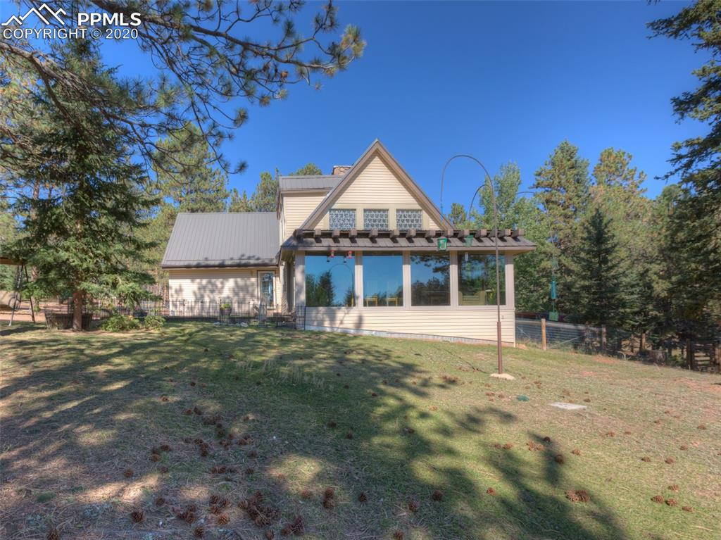 9+ acres of enchantment!  Stunning grounds with grass, conifers and aspens, a large pond and stream through property.  This is one of the most remarkable settings, with privacy, room for horses and pets, and not far from pavement.  A large shop with an automotive pit, woodstove, & power.  The entire property is fenced and cross fenced with a gated entrance.  The barn has 2 stalls and a tack room, and there's a 200+ hay bale storage building.  A perfect horse property, the horses can access the pond and there's also water by the barn.  An 8x12 greenhouse and fenced garden area with raised beds, plus a chicken coop. The home has a newer FAG furnace,  newer windows, updated kitchen with granite.  Soaring ceilings in the living room with a woodstove, a built-in dining area with granite and a large sunroom for growing plants and enjoying the views of wild turkeys and deer on the property.  Main level bedroom & full bath, laundry room and hot tub area.  Upstairs is another master with 3/4 bath and a third bedroom.  Lots of storage, including in the basement, natural gas, and a generator.  Bring your horses, pets and green thumb and start living a peaceful mountain life in Teller County.