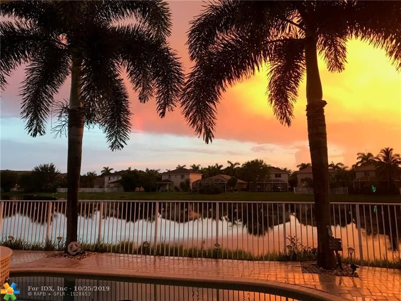 Enjoy your own piece of paradise with amazing sunsets and water views! Move in ready 3 bedroom, 2 bath, 2 car garage pool home nestled on wide water in Banyan Trails. Updated kitchen featuring white wood cabinetry, granite counters, double ovens & newer graphite stainless steel appliances. Knock down ceilings, crown molding, neutral colors, custom closets, wood laminate & tile flooring throughout.  Large master suite with custom walk-in closet and granite dual sink vanity.  Fully fenced yard with expanded Travertine deck, heated pool with jacuzzi, new salt water chlorination system & pool motor. Accordion shutters, impact garage door, great schools & great location for easy commuting. LOW HOA ($130 mo). includes clubhouse, 2 pools, fitness center and tot lot.