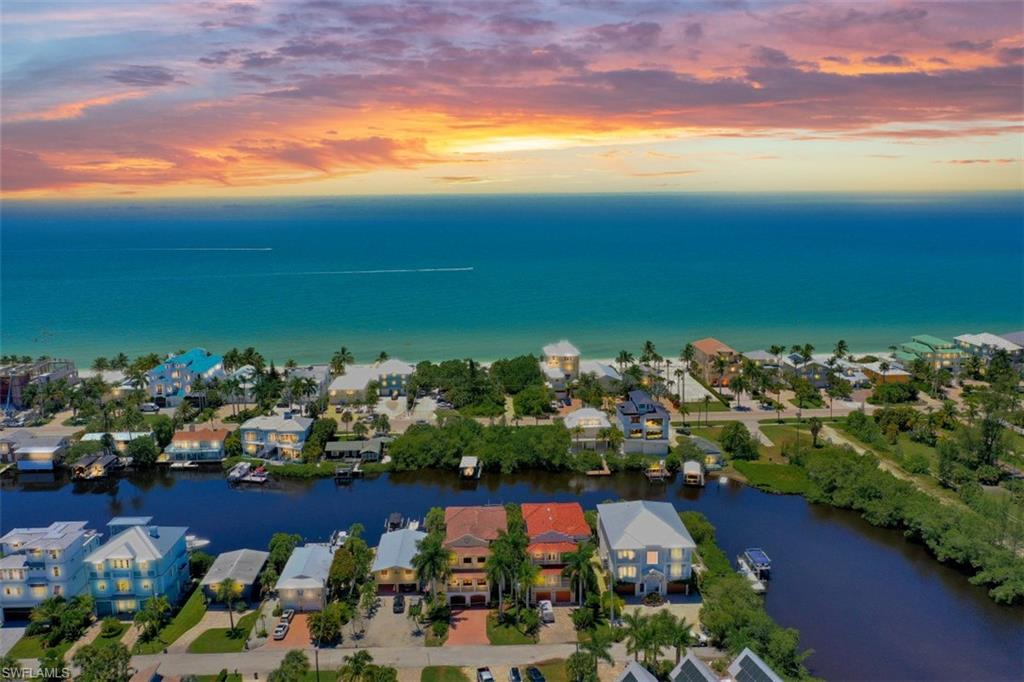 Enjoy superb sunsets and sunrises from this stunning gulf access home. With views of the Gulf, bay and canal you have extraordinary sights from every room of this house. This home features a modern open floor plan with towering coffered ceilings and new flooring. It is perfectly located just one block from the Gulf of Mexico, and directly on a navigable canal with no bridges to the Gulf. At the dead-end street, you can drop in your kayak to explore the waters of the bay. This 3 story home boasts 4 bedrooms, each with their own private bath and balcony, downstairs game/entertaining room that opens to the pool and spa and steps away from the private dock with boat lift. The home also has a 3 car garage with plenty of storage and a private elevator. Every bedroom has custom closets as well as coffered ceilings with accent lighting. The master has western views overlooking the pool and out to the Gulf. Do not miss this opportunity to own a little bit of paradise with all this home has to offer. 3D tour and video walk through available online!