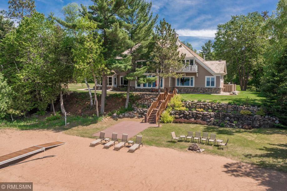 """Located on the prestigious south side of Leech Lake, this 5342 square foot luxury Leech Lake home is ALL about the beach. This impressive home features the finest materials and craftmanship, """"big water"""" views, 23' cathedral ceiling in the large main open concept living area, floor to ceiling REAL stone wood burning fireplace, hardwood floors, lakeside wall of windows, a dream kitchen, an exceptional lakeside master suite with a gas fireplace for cozy nights, a second main level bedroom suite, bonus room above the garage with a separate entrance, amazing lakeside screen porch, a REAL stone shower/changing room perfectly located for sandy toes, attached heated and insulated 3 stall garage, shuffleboard court and so much more. Arguably the best beach on Leech Lake, the beach area is 200' wide by 43' deep and even has an outdoor beach shower by the lake. This private home sits on a double lot and even has a covered harbor slip in a nearby association managed harbor. Enjoy the virtual tour!"""