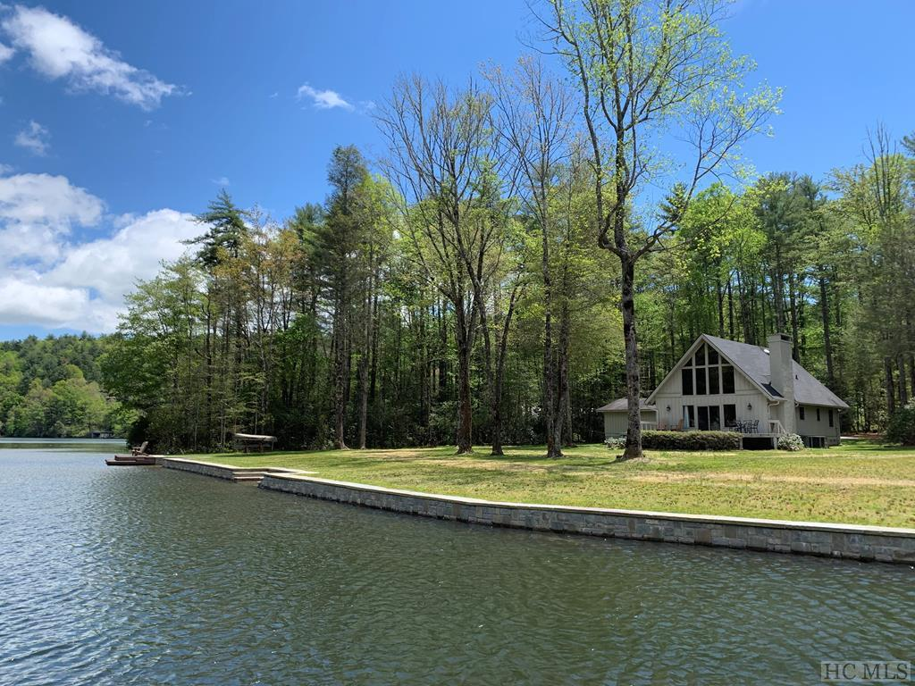 With over 290 feet of lake frontage, this absolutely prime flat double 1.76+/- acre lakefront lot with well maintained 3 BR, 2 BA cottage with new stone seawall on beautiful Lake Toxaway. Located on Skier's Cove, this park-like setting offers a unique mix of privacy and usability and features a private boat ramp as well as an area to create a double boathouse. Large trees, level entrance plus a private pond and stream on the property make this a rare opportunity on Lake Toxaway.