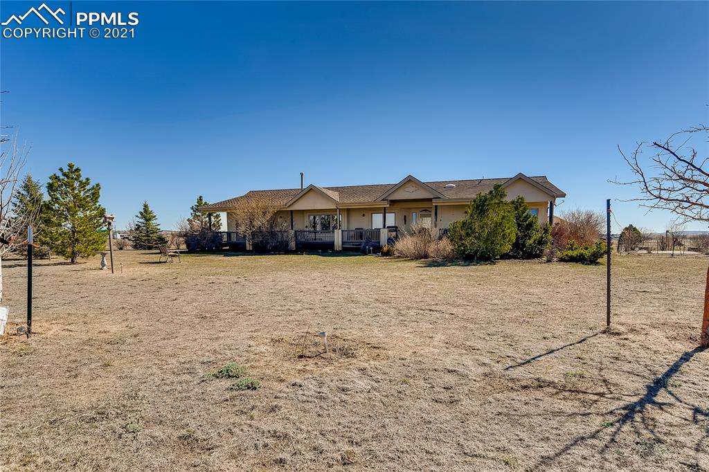 Welcome to a wonderful, one level ranch plan with two outbuildings, fenced/cross fenced on 7 acres with easy access to Springs and Hwy 24.  Located on a corner lot with beautiful Pikes Peak and Front Range views, this one owner home features three bedrooms, two baths, living room with gas kiva fireplace, separate and formal dining plus a family room.  Large kitchen and perfect for entertaining featuring granite floor tiles, granite slab counters, and lots of cook space. Easy living here with a large, covered front deck facing west to enjoy the views.  The separated master allows for privacy with a very nice bath and large, walk in closet.  Lots of built in, plus a beautiful hardwood floor along with tile. No carpet here!  Such a nice, useable floorplan yet allows for privacy.  The oversized, two car garage leads out to three fenced pastures (animals and hobbyists!)  An additional two car+ garage and a 20x28 barn with double doors make being outside a breeze.  All the work here is done for you!  Other upgrades include a Decra roof, brand new HVAC system and air conditioning, whole house surge protector, wonderful decorating accents such as the lodgepole beams and wood slatted ceilings in living room.  Mature and expertly done landscaping front and back.  All sorts of animals ok!  Come and enjoy