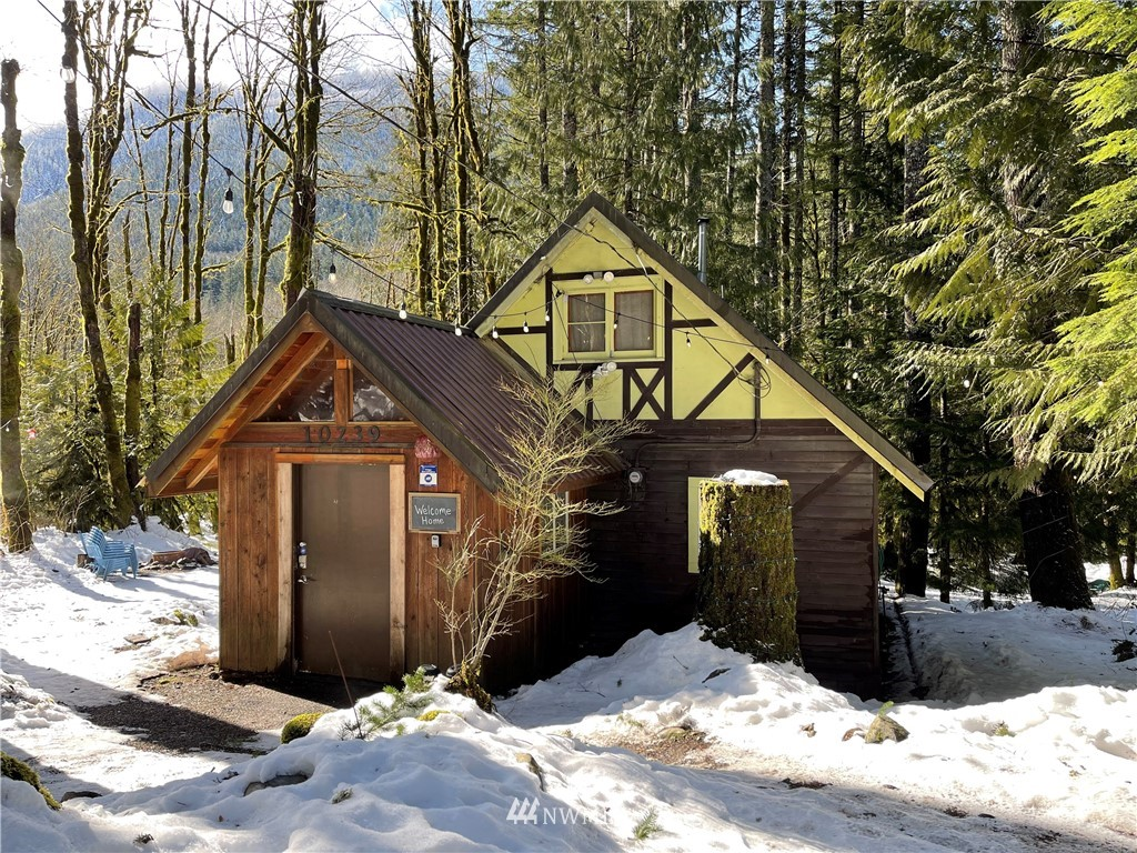 {ADVENTURE AWAITS} with this CABIN hideaway in the heart of the Alpine Lakes West/Stevens Pass Recreation Area - with terrific skiing, hiking, rock climbing, mountain biking & river sports rec areas nearby! There are 2 cabins available for lodging. The main cabin has 2 bedrooms, 3/4 bath, ample kitchen, dining & living areas, plus a covered deck to enjoy the stars & sounds of the river after the day's adventures. The smaller cabin has a kitchenette & seating area with sleeping loft above.  There is a 1 car garage/shop - great for storing your toys, with a bonus room above for overflow guests, games or ? All 3 buildings have free-standing propane stoves for heat. Private community riverfront park. Year-round access on county-maintained road!