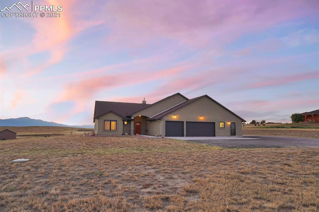 Enjoy gorgeous sunsets over Pikes Peak in this absolutely stunning rancher in eastern Colorado Springs. This home is packed with premium features and upgrades that you won't find all together anywhere else. The beautiful engineered wood floors are built to be ultra efficient for the radiant heating in the winter and remain cool in the summer. The living room features a stone fireplace, vaulted ceilings and beautiful mountain views. The kitchen is fully loaded with granite countertops, Hickory soft close cabinets, stainless steel furnishings and appliances, and gas oven. The master bedroom has vaulted ceilings, attached bathroom, and more beautiful views of the mountains. The master bathroom boasts a double vanity, a walk in shower with dual shower heads, and direct access the the walk-in closet. The over sized garage is 28 feet deep, and one of the stalls has been walled off to create a finished workshop with it's own heat, along with access to the main garage and the exterior of the home. The home also has many peace of mind upgrades such as class four roof shingles, a second forced air furnace to provide back up heat, and high efficiency insulation. On a little over 2.5 acres, you can enjoy the serene beauty of the Rockies while being just minutes from the city.