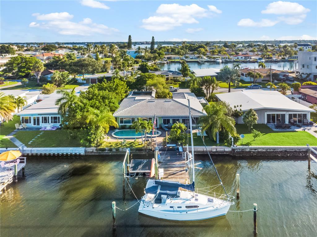 Wow! JUST REDUCED $30,000!!! Location, location, location! Don't miss this one. Welcome to beautiful Isle of Palms! Come enjoy your own slice of paradise! This gorgeous WATERFRONT POOL HOME consists of 70 feet of waterfront with direct and super-fast access to THE GULF OF MEXICO thru John's Pass. PERFECT BOATING LIFESTYLE WITH EXRA WIDE & DEEP CANALS. Just short walk or bicycle ride to some of the most beautiful beaches on the Gulf of Mexico. NO HOA FEES AND NO RESTRICTIONS. Treasure Island has so much to offer with plenty of amazing restaurants, great shopping and beautiful soft sandy beaches. John's Pass is within two miles, Downtown St. Petersburg is under an eight-mile ride. This nicely TURN-KEY almost 2,000 SQ FT property has it all! Meticulous attention to all details and all finishes. Upgraded light fixtures and ample closet space throughout. Impressive open floor plan provides fantastic water views from the kitchen, elegant living and dining rooms, guest bedroom, and master bedroom. New stainless-steel appliances and good size kitchen with ample counter seating for a large family or just friends. Enjoy magnificent sunsets across the water every evening from your own dock/marina or the fireworks on the beach! Inside laundry, outside storage, water softener, oversized one-car garage plus two-car carport and large parking pad. Lovely mature landscaping to include Mango Tree, Sea Grapes, Coco-Plums, Royal Poinciana, Queen Palms, Robellini Palms, Christmas Tree Palms, Hibiscus bushes. Most resent updates to include heated Saltwater Pool and Spa (2011), Weather Tite windows – Lanai (2019), new a/c unit (2015) with an extra ductwork and returns added plus increased the size of the ductwork (2019), tile roof (2002), newer water heater (2019), Reverse Osmosis Water Softener (2019), Sunsetter Fabric Awning (2021), stainless steel appliances (2021), vinyl fence on west side (2021) and much more! Come to see this wonderful property before it's gone!