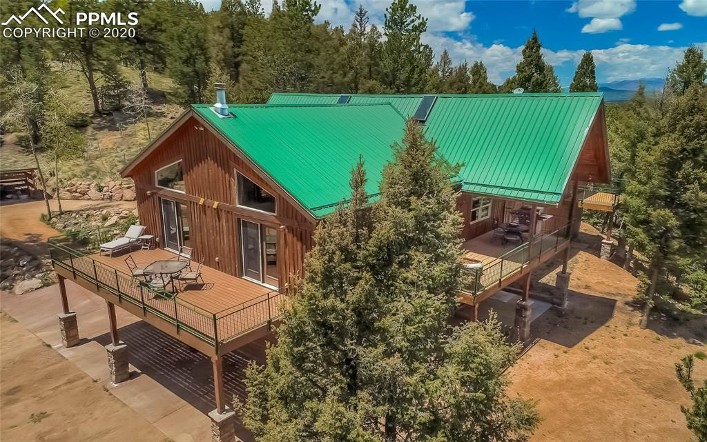 Peaceful, private, and serene…here is your Colorado mountain dream home! Only 5 miles to Divide,13 to Woodland Park, yet surrounded by 35 ACRES of pine and aspens, meadows, views, wildlife and big skies, CHECK OUT THE VIDEO! This 4,215 sq ft custom-built Rancher has 4 bedrooms, 3 baths, 3 car garage,& views from every room! The soaring Great Room is bright with natural light from the huge windows, vaulted log beam ceilings, gleaming wood floors, & safe efficient Napoleon positive pressure wood stove.The gourmet Kitchen has