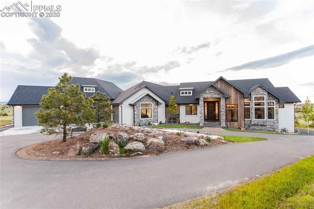 This spectacular home sits on 2.5 acres and is the builder's private residence with spectacular custom finishes throughout. Right from the start the home has beautiful mountain and golf course views, a circular driveway with a water feature island, and a custom built front door. The home includes smart home features, Alexa, automatic blinds, cameras, and whole house audio. The floor-plan is very open with large vaulted ceilings, amazing wood finishes, wide-plank wood floors, and touches of charm throughout. The kitchen features quartz countertops, a double island, high end JennAir appliances, a walk-in pantry, and double ovens. The dining room boasts gorgeous windows and walks out to the covered deck. A stunning fireplace and attractive built-ins are a wonderful touch to the great room. Off the kitchen is a hearth room, which is great for entertaining and extra space. The huge master bedroom has a lovely gas fireplace and windows that overlook the spectacular views. Off the master, is his/hers closets which lead into the laundry room. The master bathroom has large vaulted ceilings, an oversized double shower, 2 separate vanities, and an amazing tub. Completing the main level is an office, a separate homework/tech space with lovely built-ins, and a massive mud room/laundry with charming storage benches and lots of space to hang clothing. The home has a walk-out basement with 10 ft. ceilings, a spacious family room with gas fireplace and lots of additional space for entertaining. Basement has 4 other bedrooms and 2 jack-and-jill bathrooms connected. The show stopper might be the in-home regulation size racquetball court with a retractable basketball hoop, complete with storage and a drinking fountain! This home also boasts an oversized, 2600 sq. ft. 6 car garage, with a 12 ft. door allowing for RV storage. The garage also has a 30-amp RV hookup, workbench, and storage. Outside, the covered deck and patio both allow for stunning views. This home is one of a kind!