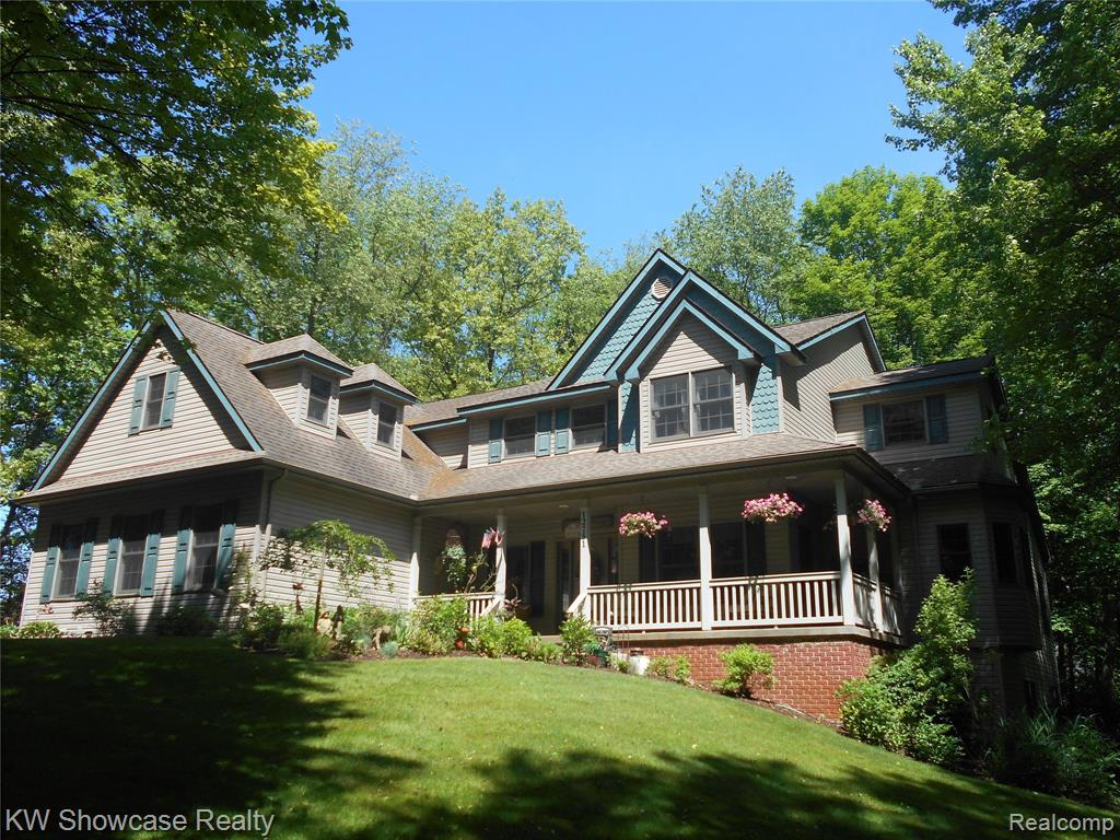 Absolutely Amazing 5700 sq ft custom Hartland colonial set on over 3.5 private acres.  This home truly has it all; an open floor plan w/gorgeous views from every window, wooded acreage w/fishing pond big enough for paddle boat and a creek from Bullard Lake running through the back of the property. Tons of charm yet full of space w/an expansive 2 story foyer & great room, 9' ceilings, huge country kitchen w/ new SS appliances & connecting dining room. 1st Floor Master w/sitting room, direct washer/dryer & huge WIC.  WICs in all bedrooms, recessed lighting thru-out, huge bonus room w/direct access to garage. Finished walkout basement makes for a great place to entertain featuring a large family room, bedroom, full bathroom and a workshop.  A nature lovers dream with lush gardens, lots of perennials, wrap-around covered front porch, sprinkler system, leaf guard gutters, composite decking. Very conveniently located yet maintains an up north feel and adjacent to Hartland Rec.
