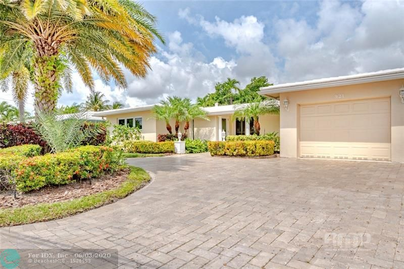 Live year round like you're on vacation, in this beautiful tropical landscaped home.  Updated, Open floor plan, with huge kitchen, that features a gas stove, SS appliances and a wet island.  Mahogany flooring throughout, with marble tile in the bedrooms.  Builti-n walk in closet in the Master bdrm.  Two separate family rooms, one can easily be used as an office/extra bdrm.  The covered Lanai extends the length of the back of the house and overlooks the pool and features an electronic screen system and beautiful wood ceiling.  Wood decking and bridge that go over your very own Koi pond, with waterfall.  Saltwater pool, travertine pavers surround the pool and in the driveway. Centrally located to schools, places of worship, grocery stores, beach and airports.  Don't delay come see it today!