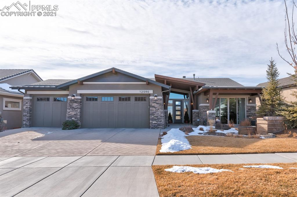 Former SaddleTree Model is sure to impress! Desirable Mountain Modern with Incredible Pikes Peak views. The architecture and curb appeal stand out with a beautiful timber and stone covered entry and patio. As you walk inside you'll immediately notice attention to detail and incredible Pikes Peak views. Open concept main level is perfect for entertaining. A great room features vaulted ceilings, timber beams, wood floors, grand fireplace, large windows. Gourmet kitchen with quartz counter tops, upgraded wood cabinetry, double wall oven, and large dining area.  Main level master with a 5 pc ensuite has great views. The main level also has a guest room with private bath, office, 1/2 bath, and large mud/laundry area. Downstairs you'll find 2 additional beds, 2 full baths, large family room, wet bar, and theater room. Enjoy the beautifully landscaped yard with incredible views from your main level covered deck or lower level walk out patio. This is an incredible home with views in a great location with ample amenities!