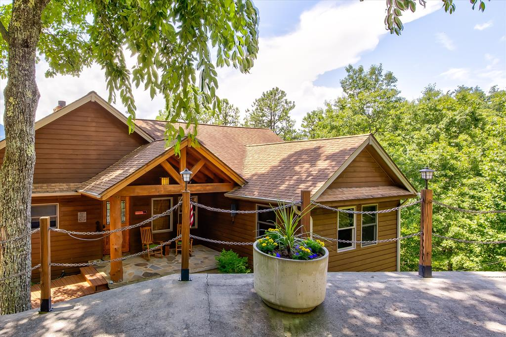 Magnificent Smoky Mountain views from this home in Cobbly Nob.  Just picture yourself sitting on the front deck watching the sun rise over the Smoky Mountains and listening to the sound of birds singing and feel a mountain breeze.  When you drive up to this home you will have the detached 2 1/2 car garage, walk down the wide staircase to the enter the antique front door and you are greeted by the spectacular view from out of the living room windows of the Smokies.  Living room has a propane fireplace hybrid  that will heat up the room in minutes, custom kitchen with five propane burners and double oven.  Huge pantry, real cherry tongue and groove flooring, and large laundry room.  Walk out to the wrap around partially covered deck.  Follow the custom railing downstairs to what could be a totally unique living area complete with its own fireplace, custom bar top along with the third bedroom and another room that could be used as a bedroom along with a custom media room.  For guests downstairs they have their own deck with the same fabulous view of the Smokies along with the hot tub.  The utility room has dual air handlers and a large commercial electric water heater.  One a/c unit was replaced in 2020.   There is also a small backup generator manual backup unit which provides emergency power to 4 circuits including the refrigerator.  This home can be a permanent residence or used as an overnight rental.   Cobbly Nob offers golf and two pools!
