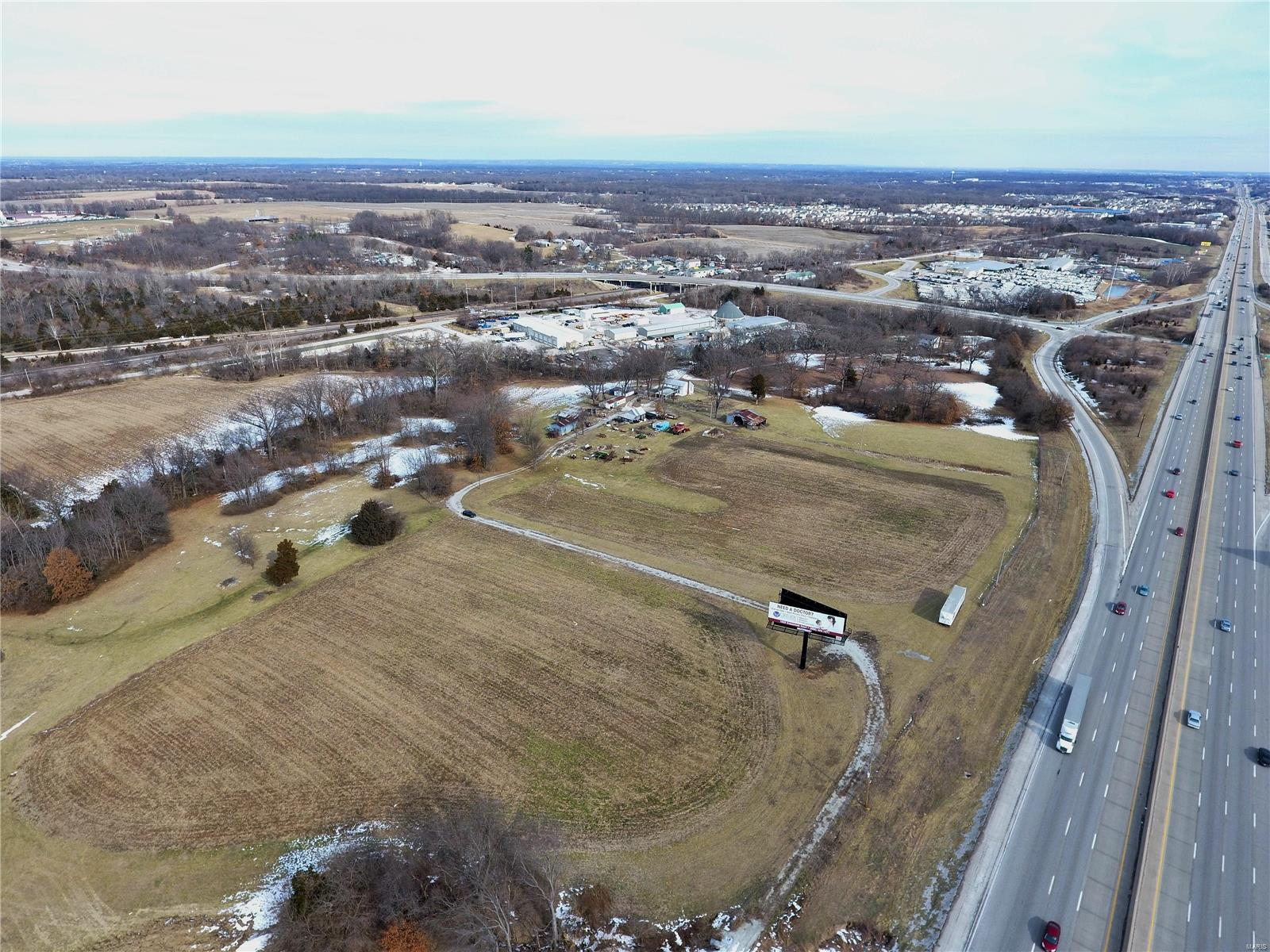 Prime property located at the intersection of I70 and Hwy A interchange in Wentzville. Located just over 1 mile to General Motors plant. Totaling 63+/- acres of gently rolling ground with a lake on site. This is a great piece for a large user or for an industrial or commercial business park. Priced at $80,000 per acre it could be a multi-use development with residential and commercial. The property currently has 2 billboard signs the produce income as well as two homes that will most likely be tear downs. 12-inch water main on E Pitman and 4-inch pressurized sewer main on E Pitman (lift station will be required). The property has 2400 feet of frontage on I70. I70 has over 75,000 vehicles per day. Located in the city limits of fast-growing Wentzville. Possible frontage road along I70 proposed via Continental Drive extension. Located just down I70 from the new 43-acre campus for Urshan College opening soon!