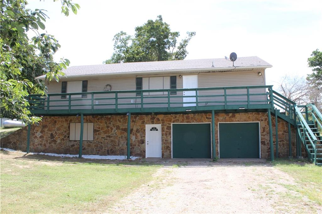 Check out this 2 story home on 5 acres MOL ~ has a newer building 50' X 40' with a 12' X 50' lean-to area (also 20' X 12' shed for man cave or lawn mower storage,  two 14' roll up overhead doors that will accommodate a RV and one 12' roll up door ~ bottom part of home is earth sheltered on the back side ~ has a 2 car attached garage plus the shop area that will garage at least 2 to 4 more ~ Lower level of home has a small living/study area and 2 rooms plus a full bathroom ~ upstairs area which has parking to access on through patio doors at upper level has a living area, kitchen, dining, master bathroom plus another bedroom with a full bathroom and utility room ~ property is fenced and cross fenced with a locked gate ~ property has a creek ~ also has building that is 30' X 40' with a lean-to for livestock with some stalls that could also be for chickens - lots of possibilities - make your appointment to take a look