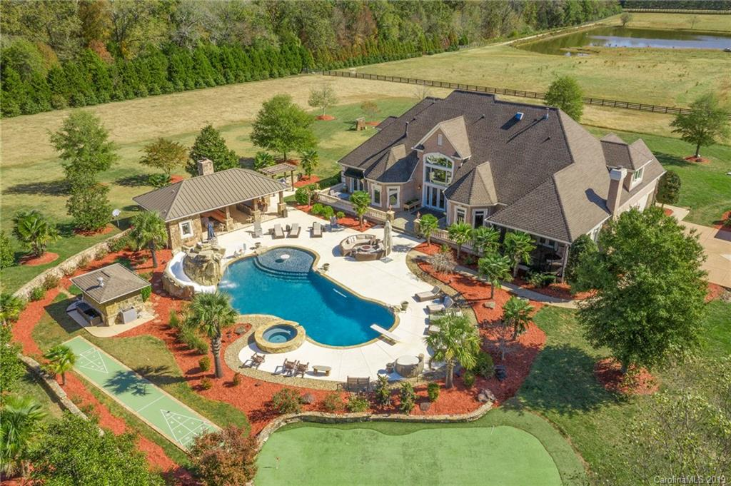 Exquisite Equestrian Estate situated on 39+/-acres. Home setback from main road by a refreshing 5-acre lake stocked with fish. Private gated drive in leads to the breathtaking estate. This home features an open floor plan with master and guest bedroom on the main level. Upstairs features Large bonus room and theater room. Attached 3-car garage with built in bar area, along with a 3-car detached garage. The rear slate veranda porch and screened in porch overlook the plush backyard. In ground pool with waterfall feature/covered pool gazebo area. Gazebo has small kitchen, full bathroom and grilling area. 8 stall barn w/ heated lounge/grooming and wash pit, half bathroom and 20 ft. breezeway along with separate guest cottage featuring wrap around porch.  An additional track of of land 74 +/- adjacent acres available for purchase with hay barn. Home is smart wired with security cameras and 1500-watt Generac generator. Don't miss this amazing opportunity to still develop on!