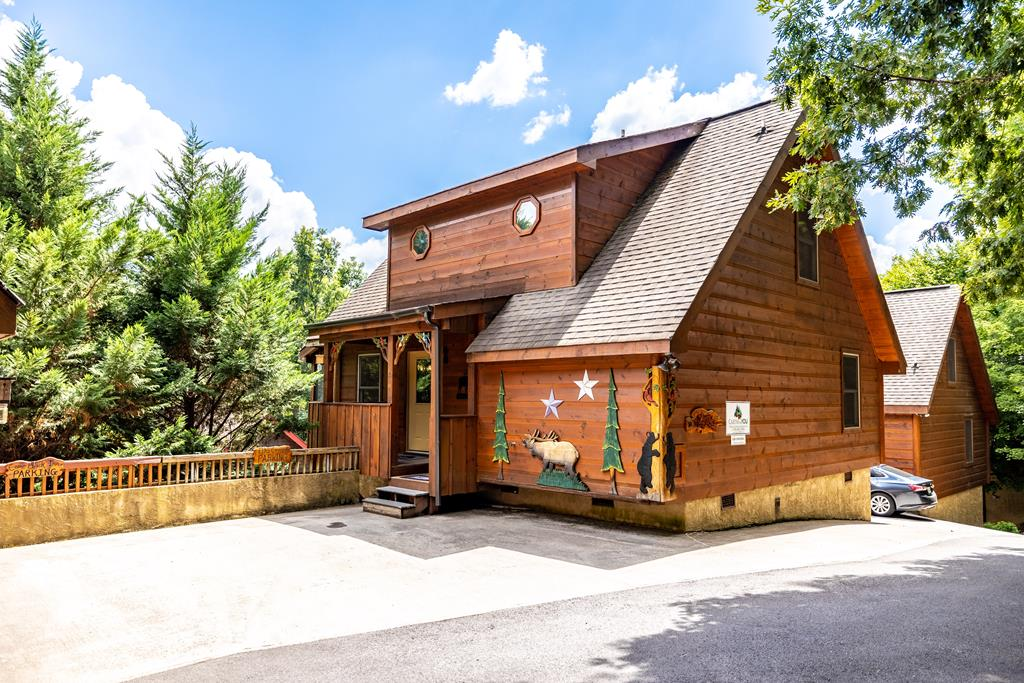 This beautiful 3 bedroom, 3 bath log cabin, with its custom wood decor detailing, looks to be right off the cover of a storybook! Located behind the iconic ''Cross'', just minutes off the main parkway in Pigeon Forge, you could not be in a more convenient location. The living room adds luxury to log cabin living with lustrous wood-planked walls, hardwood floors and a stunning, floor-to-ceiling, stacked stone gas fireplace. The living area flows into the dining area, which features a table for eight. A large breakfast bar separates the open living/dining area from the kitchen's tiled floors, stainless appliances and beautifully tiled countertops. The main level is also home to a large bedroom and full bathroom. Upstairs you will find the second and third bedrooms, each with an updated en-suite bathroom, complete with custom tiled showers and countertops. The cabin's lower level is home to a rec room packed with amenities such as a MultiCade arcade, air hockey and foosball. There's also plenty of space to relax and have fun outside! The lower level deck has new Trex decking for extra durability and the main level, screened deck has a relaxing hot tub. In the summer you'll have access to the Woodridge Village resort swimming pool, which is within walking distance.