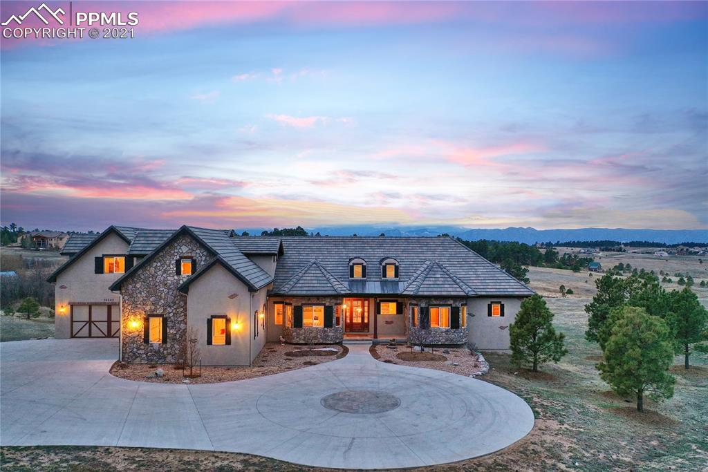 """Enjoy M/L living in a Stunning, 8500+ SF stucco and stone, two-story custom home with walkout basement, tile roof all on 2.5 acres in Settlers Ranch, PLUS each level has unobstructed, panoramic views of Pikes Peak/Front Range & neighborhood ponds & meadows; minutes from stores, eateries, schools and conveniences; includes six large bedrooms, six bathrooms, three oversized 2-car garages, + a great circular driveway, w/ reinforced concrete + an RV hookup... So many goodies! M/L living includes a gorgeous primary bedroom with separate deck and fabulous 5-pc bathroom with a HUGE walk-in closet. M/L includes extra guest bedroom with private bathroom, large study, full-size family room, which opens to the massive fully equipped kitchen with its two gourmet-sized granite islands, separate eating area, and oversized dining room - it's all beautiful, spacious and functional at the same time. The huge walk-in/mud room area from the main garages has ample room for coats, shoes, and gear is incredible as well. Hardwood floors throughout much of the main level including all stairs; vaulted ceilings, great storage, double stairways to lower lever + beautiful cabinets and built-ins. The main level is open, well defined and flows gracefully. 2 mini-kitchens areas exist on the upper and walk-out levels. Most bedrooms are oversized, with sitting areas and walk-in closets including one that can function as an additional primary with it's own separate full bathroom. The home includes 2 large office/studies or swing room: one on main lever and one on basement. Three washer/dryer rooms are conveniently located, including one in the primary bedroom suite. A spacious concrete deck with two additional wood decks allow for beautiful views and outdoor entertainment options. The oversized basement garage includes 400SF+ of storage room that is configured for storing your recreational """"toys."""" This is one of those properties you don't find very often - make an offer now!"""