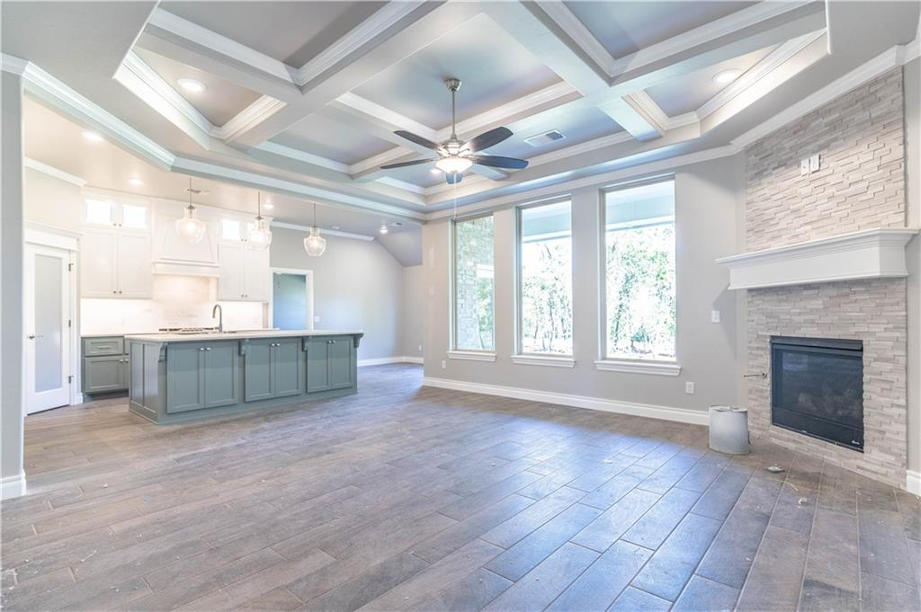 A breathtaking living space with a beautifully detailed coffered ceiling, 3 -7 ft windows, and perfectly crafted stack stone gas fireplace greet you as you step into this Hazel Bonus Room with 5 Bedrooms. This home has 2,743 Sq Ft of total living space, which includes 2,530 Sq Ft of indoor living space and 215 Sq Ft of outdoor living space. This home offers 5 bedrooms, 3 full bathrooms, and 3 car garage with storm shelter installed. Covered back patio that has 10 ft ceiling, a fireplace, fan, gas line, and cable hookups! The kitchen is opened to the living area and has cabinets to the ceiling, trashcan pullout, backsplash, 3cm quartz countertops, and stainless steel appliances. The master bedroom suite has a boxed ceiling with beautiful crown molding, dual vanities, Jetta Whirlpool tub, a large walk in shower and master closet with access to the utility room.This home includes Smart Home technology, whole home air purification, Rinnai Tankless Heater, R-44 insualtion and solarboards.