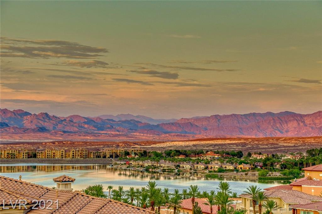 A rare opportunity awaits you in this highly upgraded fully furnished 3 bedroom condo with den that offers 180 degree views of Lake Las Vegas and it's majestic mountains. Located in the gated community of the V complete with community clubhouse, fitness center, entertainment room, putting green & BBQ area.The unit features travertine flooring, crown molding, fireplace a single-attached garage & ceiling fans. The kitchen offers granite counters, recessed lighting, stainless steel appliances and a built-in wine fridge. The Primary bedroom with a walk-in closet and glass sliding door, allows access to a private balcony overlooking the lake. The primary bath has stone tile flooring throughout, a separate, large walk-in shower and a separate jetted tub. Nuvo saltless water softener, tankless water heater are included as well as Sports Club membership valued at $10,000. Resort style living at it's finest. Don't miss this opportunity!